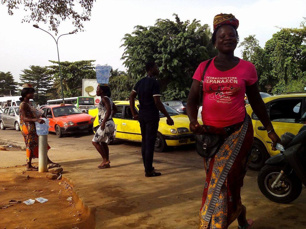 Affoué s'est déjà lancé dans une course effrénée, se faufilant entre les véhicules, sachets d'eau dans les mains, pour arracher un client chauffeur de taxi, des griffes de ses concourantes.
