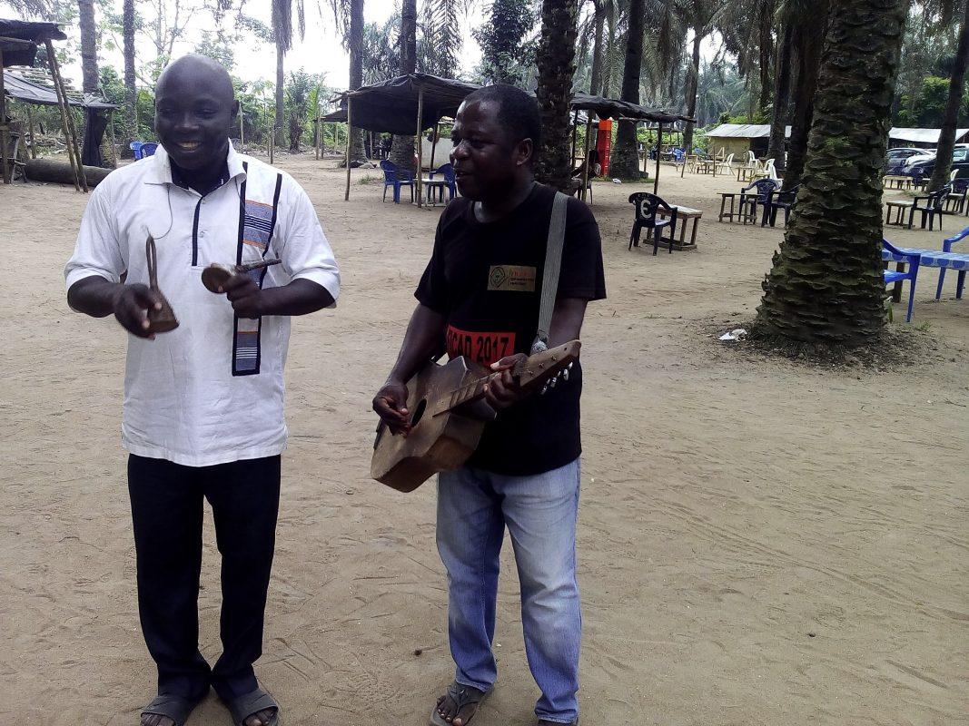 Où que vous soyez assis, vous ne pouvez manquer ces deux chansonniers baoulé qui viennent à vous. Ils vous encensent en musique, lui pinçant passionnément les cordes d'une guitare artisanale